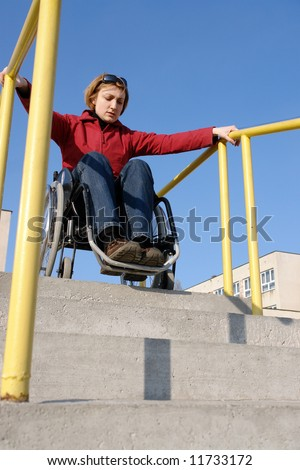 Handicapped woman on wheelchair going down the concrete stairs