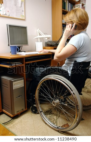 Handicapped woman on wheelchair working at home with computer talking on the phone