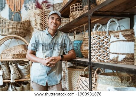 handicraft business owner with his hands leaning back on a shelf while in a handicraft shop with crafts in the shelf background