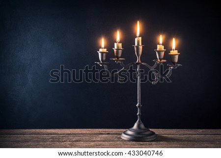 handicraft candelabrum with burning candles on old wooden table against art dark background #433040746