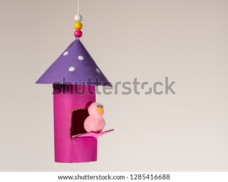 Handicraft of a colorful bird house and a small bird made of toilet paper roll by a child, hanging on a thread with beads Сток-фото ©