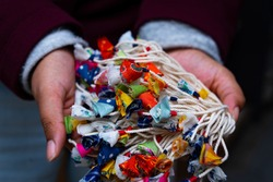 Handicraft woman with silk flower on her hand. Handicraft silk flower on a traditional Indian costumes in the workshop.