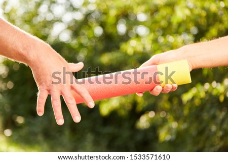 Handing over a baton as a symbol of teamwork and teamwork