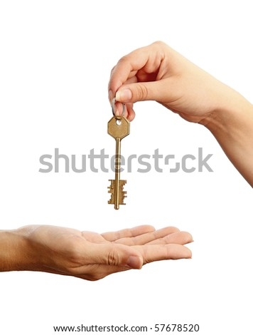 Handing over a key. Female hand holding a key and handing it over to another woman. Concept picture.