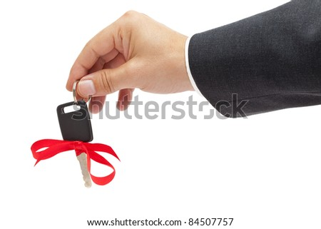 Handing over car key with red bow as a present