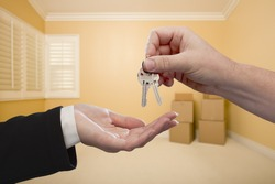 Handing Over the House Keys To A New Home Inside Empty Room.