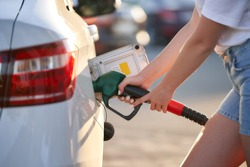 Handle fuel nozzle to refuel. Female hands hold a refueling nozzle stuck into a gas tank of modern car. Close-up. woman fills the gas tank