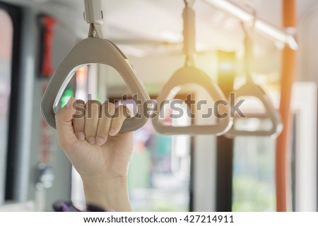 Handle on ceiling of bus,handle on a train,The handle on the MRT, prevent toppling.underground railway system or metro,people holding onto a handle on a train and the bus,selective focus,vintage color