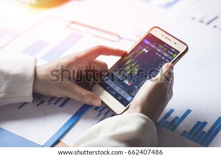 Handle the phone to check the stock with Sunset light background. - Shutterstock ID 662407486