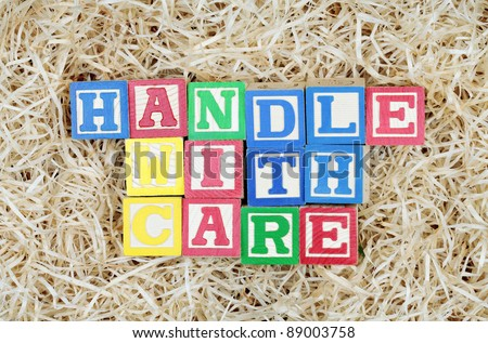Handle With Care Spelled Out by Blocks in Packing Material
