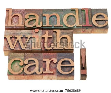 handle with care warning in vintage wood letterpress printing blocks, isolated on white