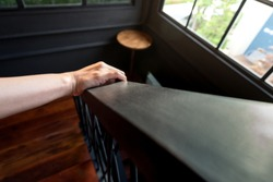 Handling on wooden handrail while going down stair in luxury mansion. Close up on human action.