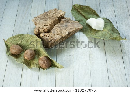 handmade african black soap and ingredients, shea butter nuts, leaves and white shea butter