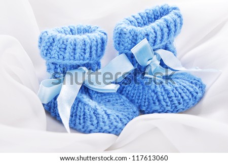 Handmade  baby booties isolated on a white silk background