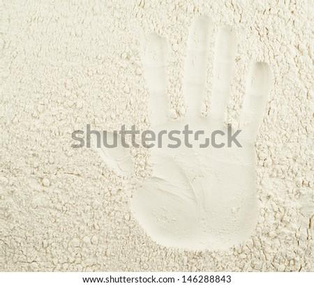 Handmade baking concept as a hand imprint over wheat flour background