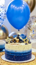 Handmade birthday cake on a blurred background with balloons and sparkles. Cheesecake cake, blue and gold accents. Festive background for postcard, holiday, birthday, anniversary, 18 years.