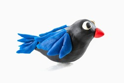 Handmade black bird with blue wings and red beak made out of play dough, play clay