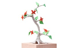 Handmade bonsai tree on white. Origami flowers and leaves on twisted trunk. Result of paper craft.