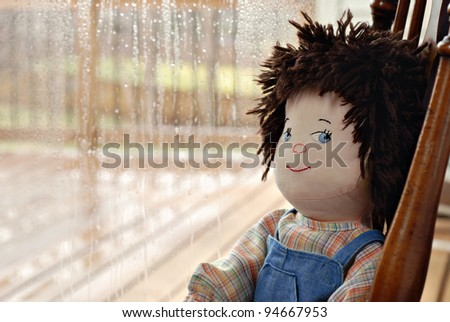 Handmade boy rag doll with cute sideways expression sitting alone next to a rainy window.  Closeup with shallow dof and copy space. - stock photo
