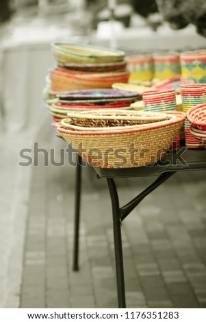 Handmade Brightly Colored Woven Basket Bowls on a Display Table For Sale, Black and White with Selective Color #1176351283