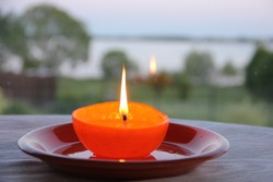 Handmade candle used orange and olive oil on the plate. River and trees on the background