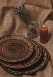 Handmade ceramic craft ware. Rustic napkin and kitchen tools. Plate on a wooden stand with lavender and candle. Handmade ceramic dishes