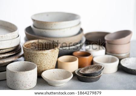 handmade ceramics, empty craft ceramic plates and bowls on light background  Stock photo ©