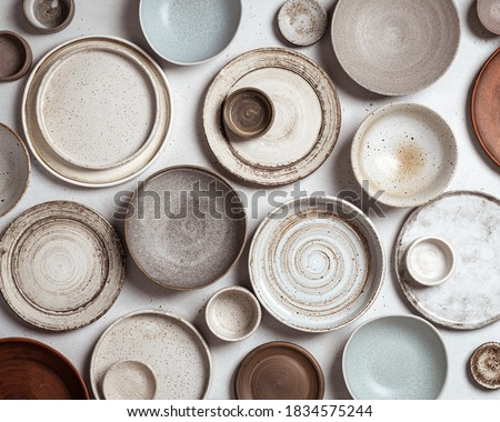 handmade ceramics, empty craft ceramic plates and bowls on light background, top view Foto stock ©