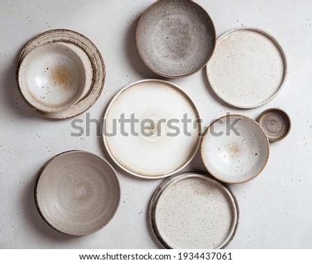 handmade ceramics, empty craft ceramic plates on light background top view Stock photo ©