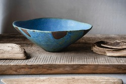 Handmade ceramics in the style of wabi sabi. Blue clay bowl with an abstract pattern.