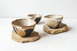 Handmade ceramics in the style of wabi sabi. Brown clay bowls with an abstract pattern.