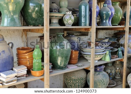 Handmade ceramics on a wooden shelf at workshop in Fes, Middle Atlas, Morocco, North Africa