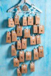 Handmade Christmas Advent Calendar to do by yourself at home on blue wooden background
