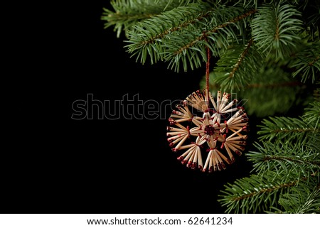 Handmade christmas ornament on a pine christmas tree, black background, a lot of copyspace available