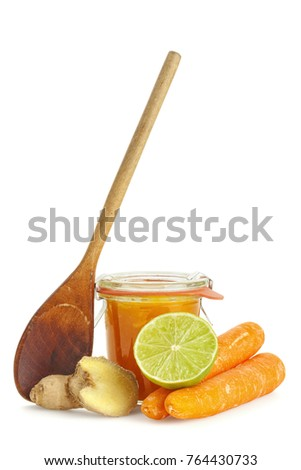 Handmade chutney with carrots, ginger, lime in a jar with wooden spoon isolated on white background