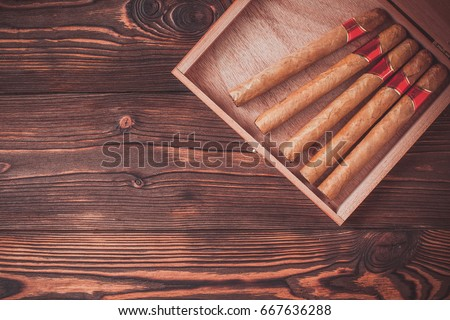 Handmade cigars on a wooden background