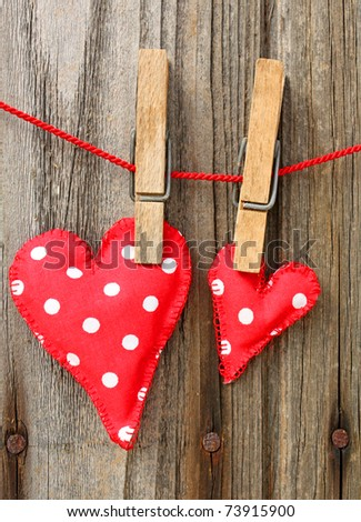 Handmade clothes hearts hanging on  line against old wood-grain wall