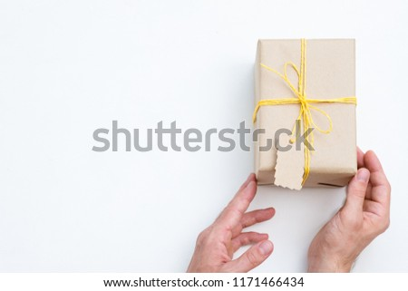 handmade craft present. heartfelt congratulation and reward for a special person. hands holding gift wrapped in paper and tied with yellow twine. festive package on white background.