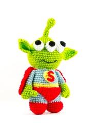 handmade crochet green alien three eyes super hero doll on white background, turn right side