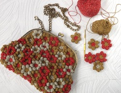 Handmade crochet purse on white surface along with yarns, crochet flowers, and crochet hook. It is made of crochet flowers joined one to another by hand sewing. Concept of art, design, and creativity.