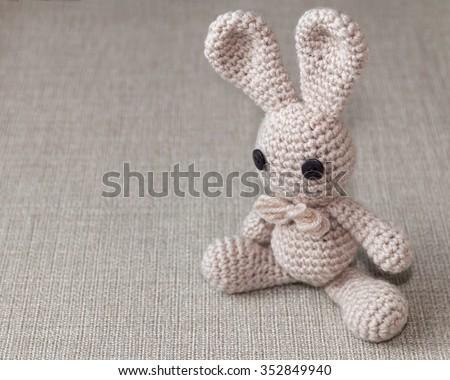 Handmade crochet rabbit toy on burlap rustic background. Amigurumi doll, space for text