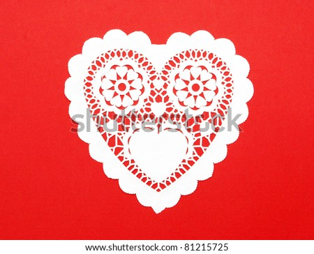 Handmade Cutout Fancy Paper Heart doily isolated on red background