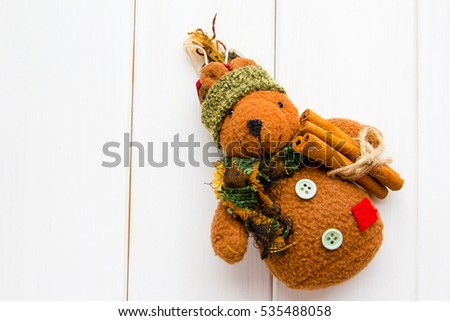 Handmade design Christmas teddy bear toy with cinnamon sticks at white wooden background