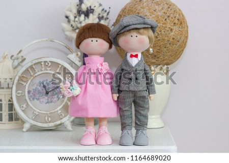Handmade dolls of pink and gray color in a dress and suit in a hat on the head on the background of the interior of your room with flowers in your hand. Sweet couple, eternal love