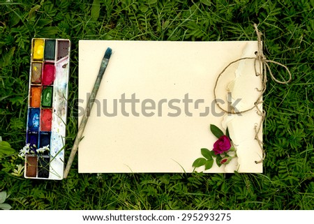 handmade drawing pad with flowers and leaves of wild rose, watercolor paints and brush on the background of grass