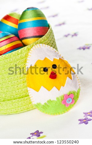 Handmade Easter decorations on an embroidered tablecloth - stock photo