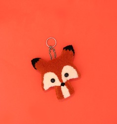 Handmade embroidered key holder in fox shape with a metal ring and chain, top view on red background