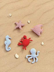Handmade fabric toys on sandy background. Baby educational toys. Acquaintance with different sea animals. Toy crab, octopus, starfish, sea horse and fish