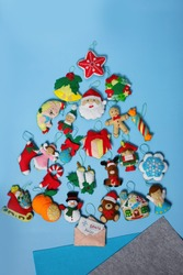 Handmade felt Christmas ornaments: elf, bear, nutcracker, snowman, santa claus are on a blue background. Concept of hand sewing, cute Christmas heroes, Christmas tree.