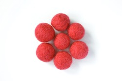 Handmade felted balls of worsted merino wool, red rusty crimson carmine firebrick, isolated on white background, flat lay top view of felt ball, a concept of dry or wet felting creative arts and craft